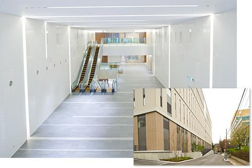 後ろ:2階エントランス吹き抜け 1号館と2号館を結ぶ連絡通路に続く木漏れ日をイメージした空間 手前:1号館北側(左)の向かいは総合医科学研究棟(右)